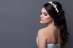 Retratos delicados bonitos da menina da noiva em um vestido de casamento branco com penteado da noite com uma borda das flores em Fotos de Stock