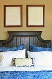 Retratos em branco na parede acima da cama fotografia de stock royalty free