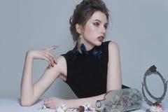 Retratos surrealistas de una muchacha con las flores secas, el maquillaje y la joyería Imagen de archivo
