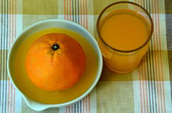 Retreat with orange juice and porcelain juicer on dish towel Stock Photography
