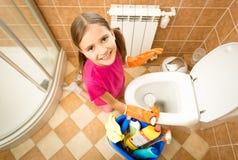 Retrete sonriente de la limpieza de la muchacha con el cepillo y mirada de la cámara Imagen de archivo