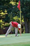 Retrieving Ball. Male golfer bends to retrieve golf ball from hole Royalty Free Stock Photo