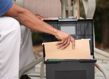 Retrieving Records. A home based worker on his deck pulling files from a container Royalty Free Stock Photography