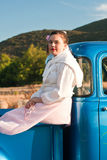 Retro 1950s teen in classic blue truck. A multicultural 15 year old teen dressed in a pink poodle skirt, white blouse, sweater tied around neck, pink pearls, and Stock Photo