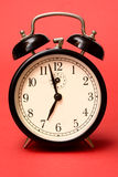 Retro alarm clock. (isolated on red Royalty Free Stock Photos