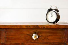 Retro alarm clock. On bedside table,  background white wooden wall Royalty Free Stock Images