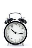 Retro alarm clock. Black metal retro alarm clock with isolated white background Stock Image
