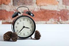 Retro alarm clock on the brick wall background. Stock Image