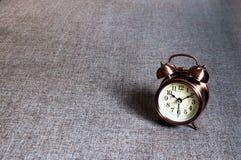 Retro alarm clock. Bronze metalic retro style alarm clock on gray textile surface cushion royalty free stock photography
