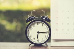 Retro alarm clock and calendar on wooden table Royalty Free Stock Photo