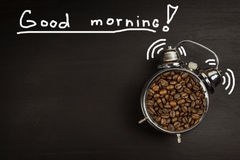Retro alarm clock with coffee beans. Morning coffee after waking up. Wake up. Stock Photo