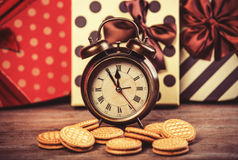 Retro alarm clock with cookie Royalty Free Stock Images