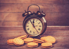 Retro alarm clock with cookie Royalty Free Stock Image