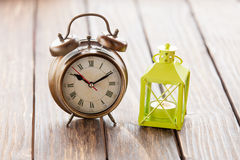 Retro alarm clock and decorate lamp. Royalty Free Stock Photography