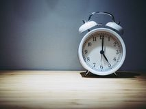 Retro alarm clock with five o`clock. Old style filtered photo royalty free stock photography