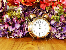 Retro alarm clock with flowers background Royalty Free Stock Image