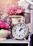 Retro alarm clock with flowers. Royalty Free Stock Photo