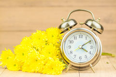 Retro alarm clock and  flowers Royalty Free Stock Photography