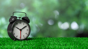 Retro alarm clock on grass. With abstract green bokeh background Stock Photography