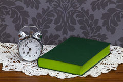 Retro alarm clock and green book Stock Photography