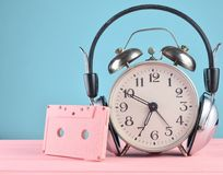Retro alarm clock with headphones and audio cassette on wooden table on pastel background, copy space. Retro alarm clock with headphones and audio cassette on Royalty Free Stock Image