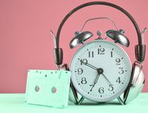 Retro alarm clock with headphones and audio cassette on wooden table on pastel background, copy space. Retro alarm clock with headphones and audio cassette on royalty free stock photo
