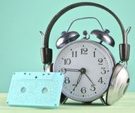 Retro alarm clock with headphones and audio cassette on wooden table on pastel background, copy space. Retro alarm clock with headphones and audio cassette on royalty free stock photography