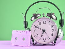 Retro alarm clock with headphones and audio cassette on wooden table on pastel background, copy space. Retro alarm clock with headphones and audio cassette on stock photo
