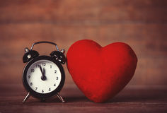 Retro alarm clock and heart shape on wooden table. Stock Photo
