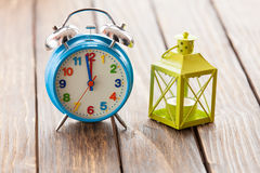 Retro alarm clock and  lamp on wooden table. Stock Photos
