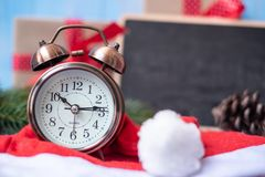 Retro alarm clock with Merry Christmas gift box or Present and Santa Claus hat on blue wooden background. Preparation for Boxing Day, Happy New Year and Xmas royalty free stock photography
