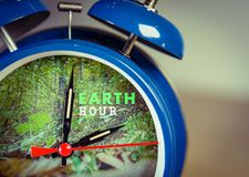 Retro alarm clock with nature background symbolizing Earth hour. Towards the end of March or earth day on April 22 stock photos