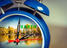 Retro alarm clock with nature background symbolizing Earth hour. Towards the end of March or earth day on April 22 royalty free stock photography