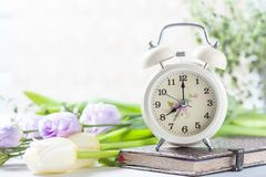 Retro alarm clock, notebook and spring flowers. royalty free stock image