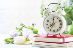 Retro alarm clock, notebook and spring flowers. stock images