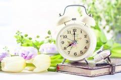 Retro alarm clock, notebook and spring flowers. stock image