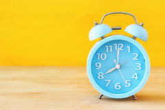 Retro alarm clock over yellow background.  Stock Images