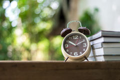 Retro alarm clock pointing on 10:00 o`clock with book. Or memo on wood table Stock Image