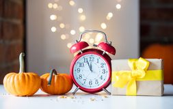 Retro alarm clock with pumpkins and gift box near Fairy Lights Stock Photo