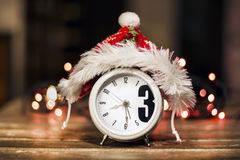 Retro alarm clock with red christmas hat. On a bokeh background stock photos