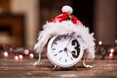 Retro alarm clock with red christmas hat Royalty Free Stock Photos