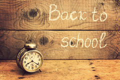 Retro alarm clock on a rustic table and Back to school inscription Royalty Free Stock Photography