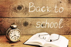 Retro alarm clock on a rustic table and Back to school inscription Stock Photos