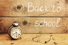 Retro alarm clock on a rustic table and Back to school inscription Stock Photo