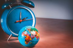 Retro alarm clock with a small world globe ball symbolizing Earth hour. Towards the end of March or earth day on April 22 royalty free stock photo