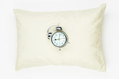 Retro alarm clock on the soft feather pillow close-up on a white. Background Royalty Free Stock Image