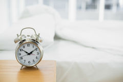 Retro alarm clock standing on a bedside table Stock Images