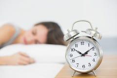 Retro alarm clock standing on bedside table Stock Photo