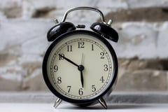Retro alarm clock on table on brick wall background royalty free stock photos