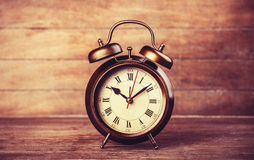 Retro alarm clock on a table. Royalty Free Stock Images
